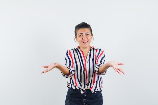 Femme en chemise, jupe écartant les paumes ouvertes et à la confusion