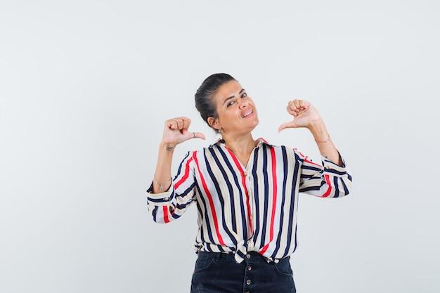 Femme en chemise, jupe pointant sur elle-même avec les pouces et à la fierté