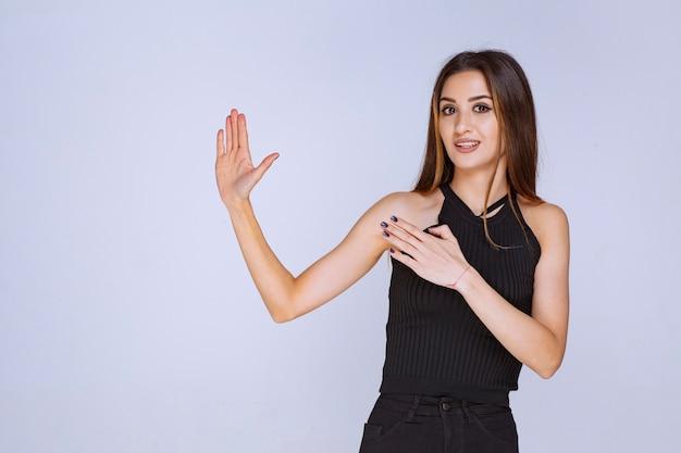 Femme en chemise noire arrêtant quelque chose.