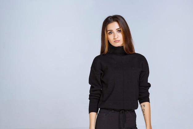 Femme en chemise noire donnant des poses attrayantes et neutres.