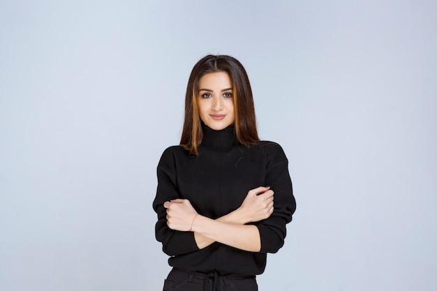 Femme en chemise noire donnant des poses neutres et coquettes.