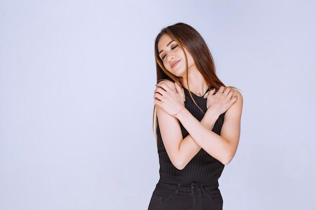 Femme en chemise noire donnant des poses séduisantes et attrayantes.