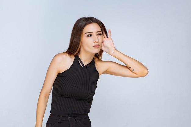 Femme en chemise noire essayant d'écouter attentivement.