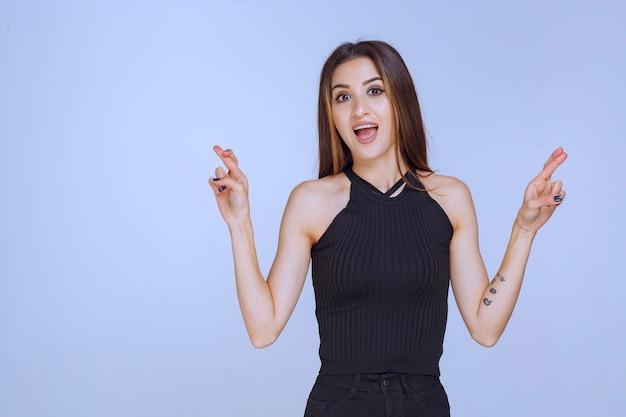 Femme en chemise noire faisant signe de croix de doigt.