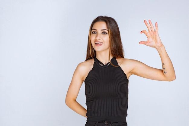 Femme en chemise noire montrant les dimensions estimées d'un objet.