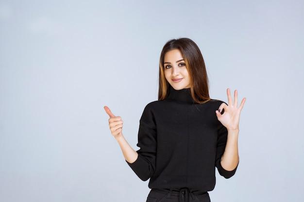Femme en chemise noire montrant un signe positif de la main.