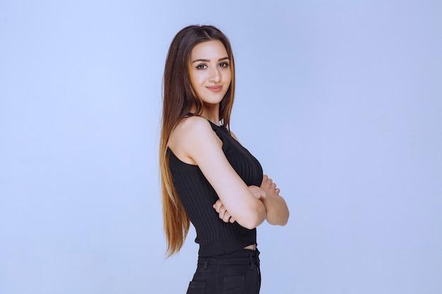 Femme en chemise noire souriante.