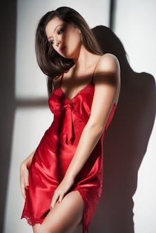 Femme en chemise de nuit rouge avec lumière de fenêtre