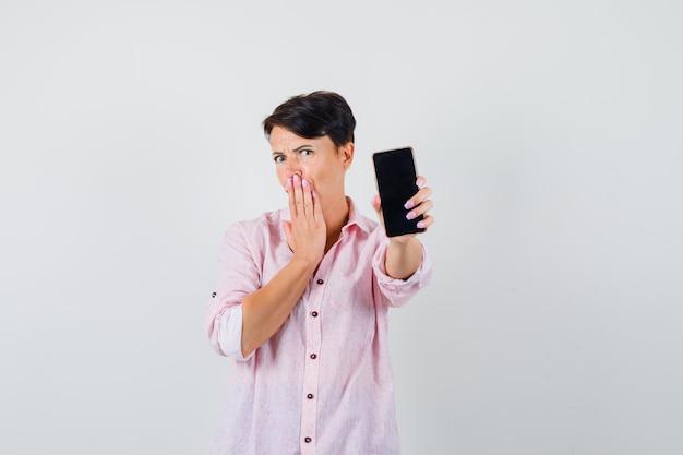 Femme en chemise rose montrant un téléphone mobile et à la surprise, vue de face.