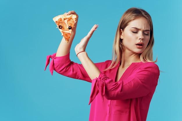 Femme en chemise rose pizza holding fast food régime fond bleu