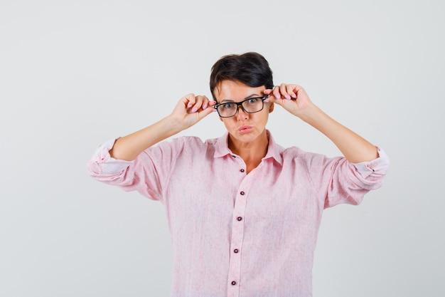 Femme en chemise rose regardant à travers des lunettes et à la recherche intelligente, vue de face.