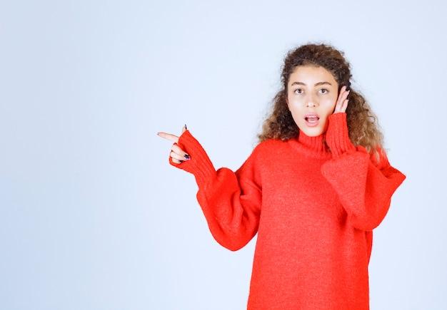 Femme en chemise rouge pointant vers quelqu'un ou quelque part avec un visage émotionnel sur bleu.
