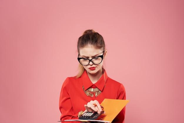 Femme en chemise rouge portant des lunettes bloc-notes dans les mains de travail professionnel. photo de haute qualité