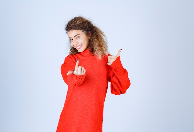 Femme en chemise rouge remarquant quelqu'un devant et envoyant de l'énergie positive.