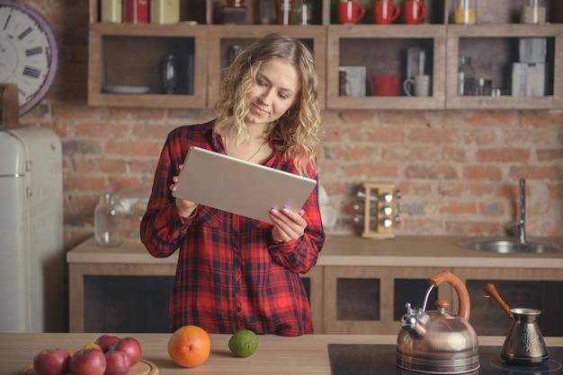 Femme en chemise rouge avec une tablette numérique dans la cuisine