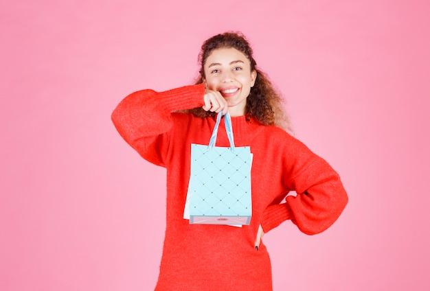 Femme en chemise rouge tenant plusieurs sacs colorés.