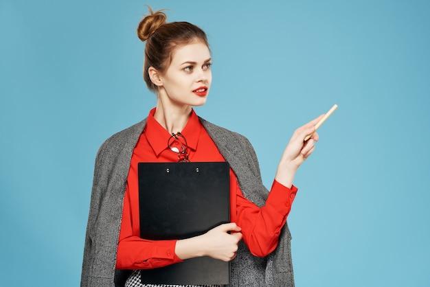Une femme en chemise rouge avec une veste tient une feuille de papier fond bleu espace copie