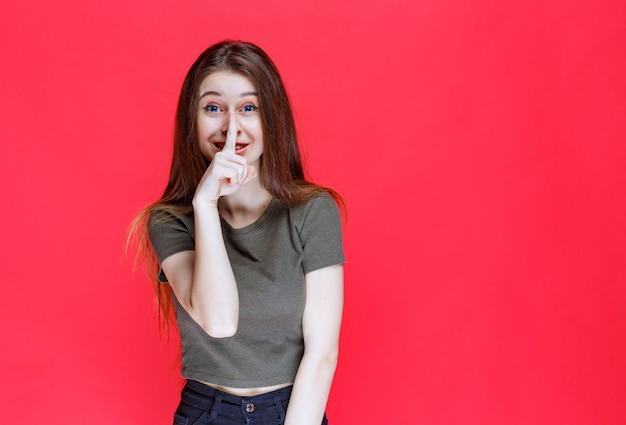 Femme en chemise verte demandant le silence.