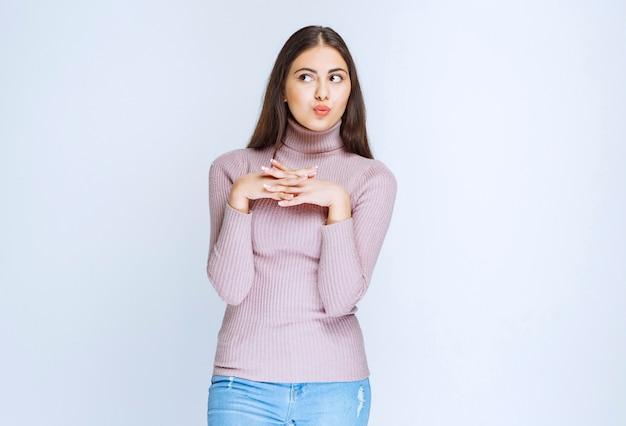 Femme en chemise violette donnant des poses neutres.