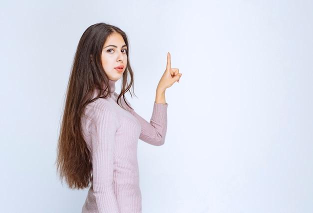 Femme en chemise violette montrant quelque chose au-dessus.