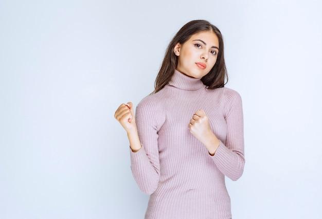 Femme en chemise violette montrant ses poings puissants.
