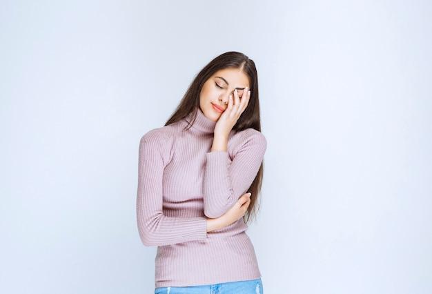 La femme en chemise violette a sommeil ou a mal à la tête.