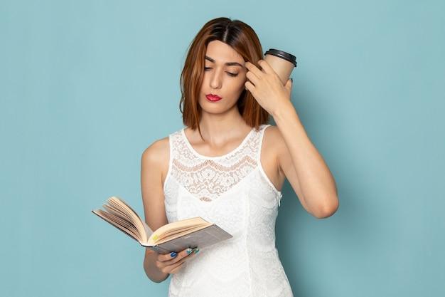 Femme en chemisier blanc et jean bleu tenant une tasse de café et un livre