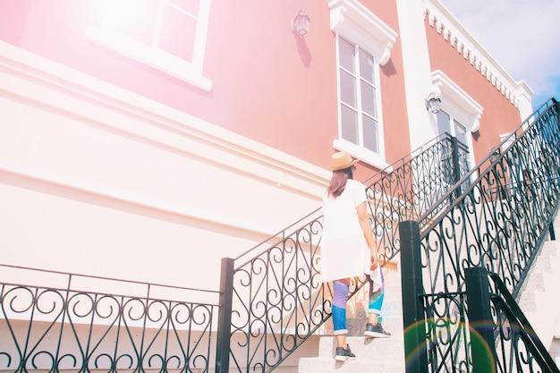 Femme en chemisier blanc et jeans marchant dans un bâtiment classique avec une perspective attrayante