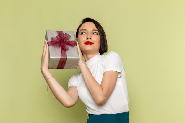 Femme en chemisier blanc et jupe verte tenant la boîte présente
