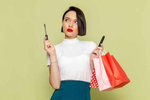 Femme en chemisier blanc et jupe verte tenant des paquets de courses et du mascara