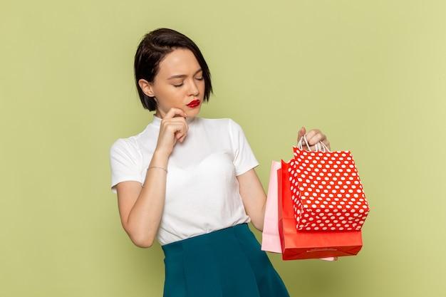 Femme en chemisier blanc et jupe verte tenant des paquets shopping