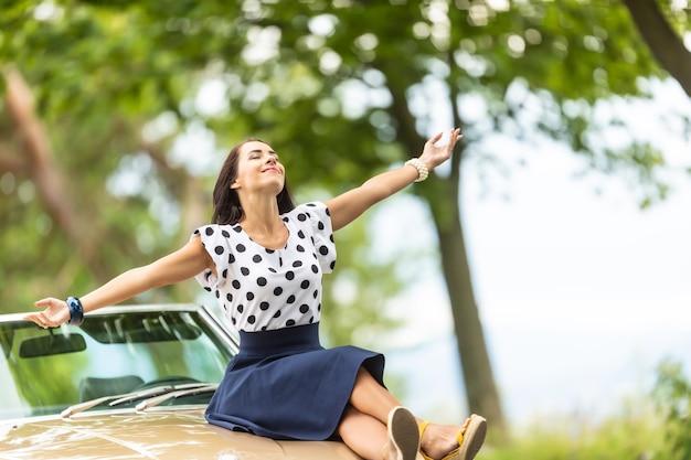 Femme en chemisier et jupe à pois est assise sur le capot d'une voiture cabriolet, les bras ouverts, profitant de l'été.