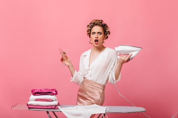 Femme en chemisier et jupe regarde avec indignation à l'avant et pose avec du fer, du verre à martini