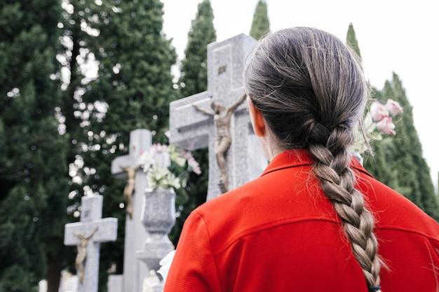 Femme avec chemisier rouge et tresse de cheveux priant un être cher au cimetière