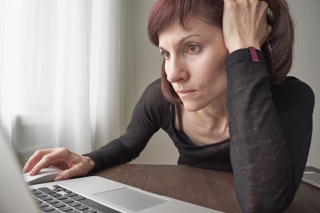 La femme cherche des informations sur internet, nerveuse, concentrée.