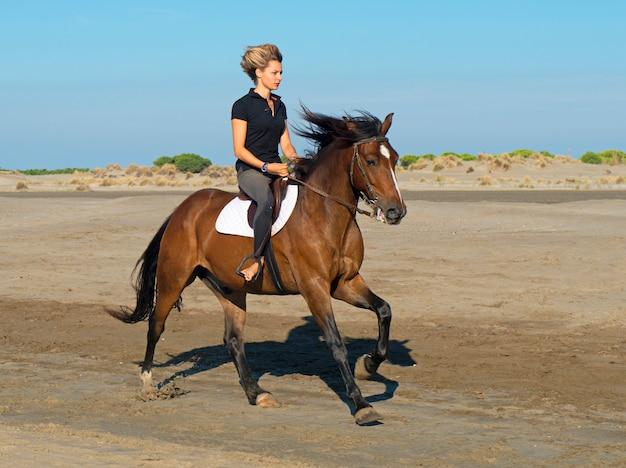 Femme cheval sur la plage