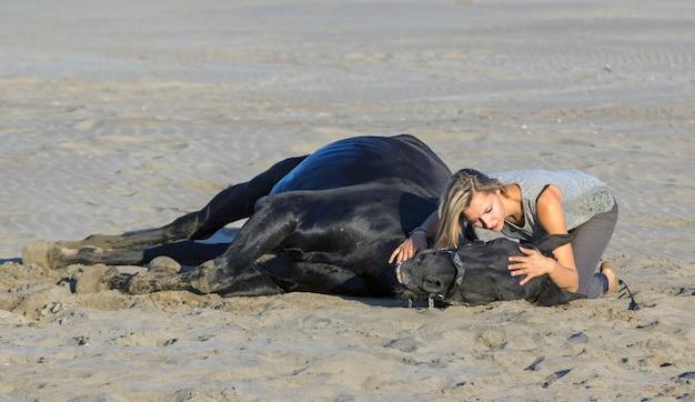 Femme et cheval sur la plage