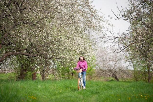 Femme chevauchant un vélo blanc vintage avec un panier de fleurs