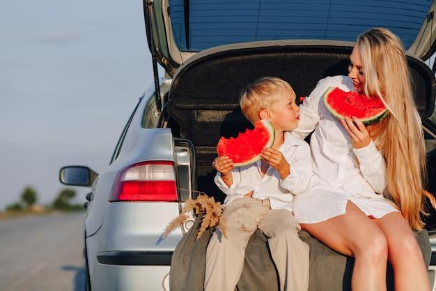 Femme cheveux assez blonds avec petit fils blond au coucher du soleil se détendre derrière la voiture et manger la pastèque. été, voyages, nature et grand air à la campagne.