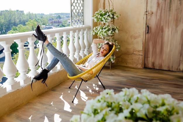 Femme cheveux bruns profitant de sa terrasse confortable. jeune femme allongée sur une chaise, se détendre à la maison.