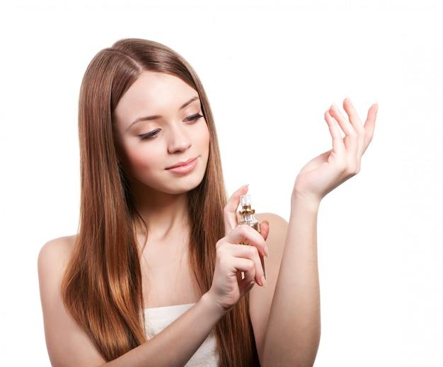 Femme, à, cheveux bruns, pulvérisation, parfum, sur, elle, poignet