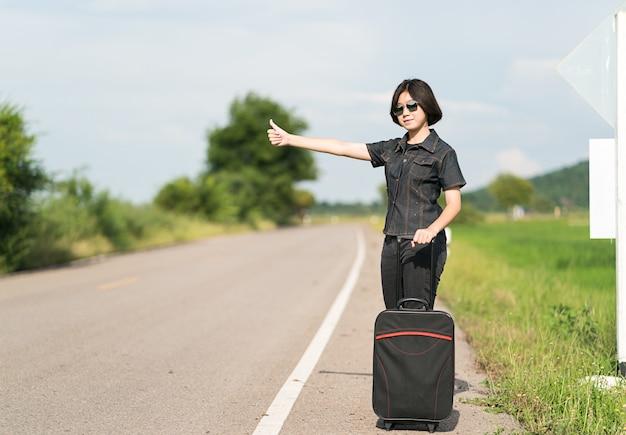 Femme cheveux courts avec bagage faisant de l'auto-stop et bravo