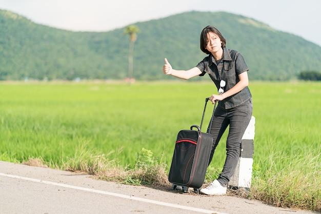 Femme cheveux courts avec bagages faisant de l'auto-stop et bravo