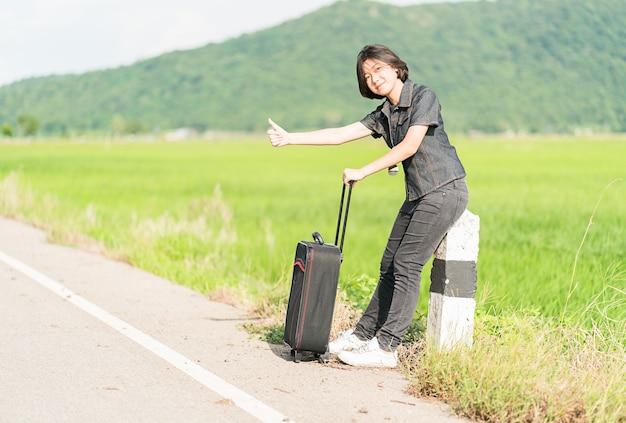 Femme cheveux courts avec des bagages faisant de l'auto-stop et les pouces vers le haut