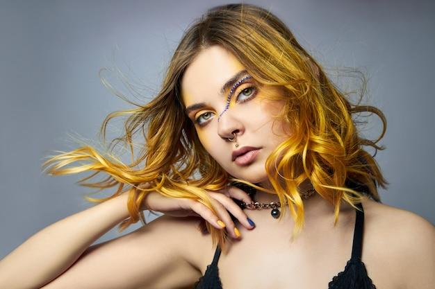 Femme avec des cheveux créatifs de coloration jaune et maquillage avec strass