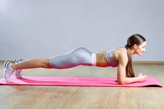 Femme cheveux longs faisant de l'exercice statique de planche dans une salle de sport allongé sur un tapis