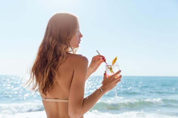 Femme avec les cheveux longs, tenant un verre de vin avec un cocktail, passer des vacances
