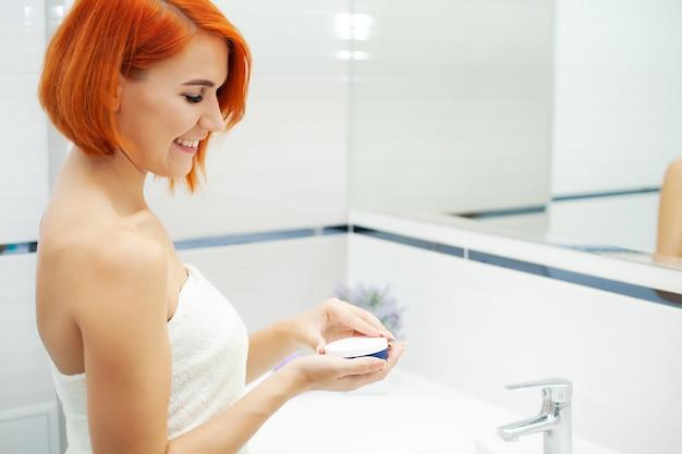 Femme, à, cheveux rouges, dans, salle bains, utilisation, soin, produits