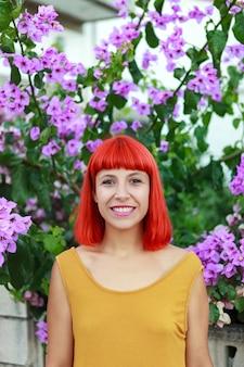Femme cheveux roux avec de belles fleurs de fond