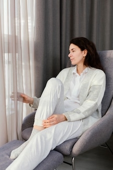 Femme, chez soi, regarder dehors, fenêtre